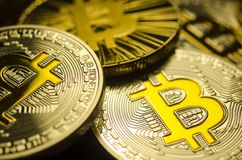 Macro view of shiny coins with Bitcoin symbol on dark background Stock Image