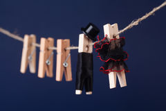 Macro view wooden clothespin characters on dark blue background. Bride in black red dress and groom character man suit Royalty Free Stock Photography