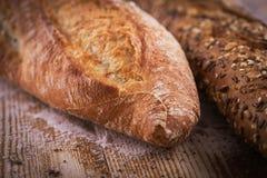 Macro vista del pane croccante fresco delle baguette con i semi di girasole ed altri semi sullo scrittorio di legno rustico Immagine Stock