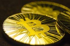 Macro vue des pièces de monnaie brillantes avec le symbole de Bitcoin sur le fond foncé Photo libre de droits