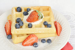 Macro waffles with blueberries and strawberries Royalty Free Stock Photos