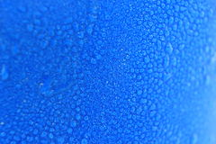 Macro water drops background on blue cup. Royalty Free Stock Photos