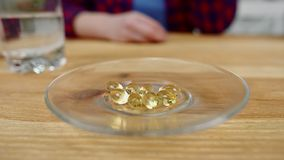 Macro woman hand takes yellow capsule from plate and returns. Macro woman hand takes large yellow capsule from transparent plate on table with water glass and stock video