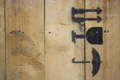 Macro wood texture spray painted with black fragile icons. This is a neat macro shot of a wooden crate that has black spray painted icons identifying the package Royalty Free Stock Photos