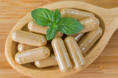 Macro of wooden spoon full of herbal medicine in clear capsules, ideal for Homeopathic remedies stock image