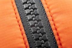 Macro zip-lock noir avec le fond orange de toile Image stock