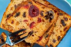 Macrobeeld van een cakeplak met vruchten en een dessertvork Fruitcake met rozijn en kers stock foto
