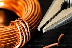 Macrobeeld van een rol van koperdraad en een paar naald-neus buigtang stock foto's
