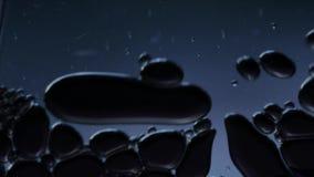 Macroclose-up van elementen in water of olie, abstracte achtergrond 4k UHD stock video