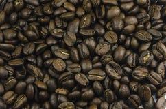 Macroclose-upmening van heel wat koffiebonen die op lijst leggen Royalty-vrije Stock Afbeelding