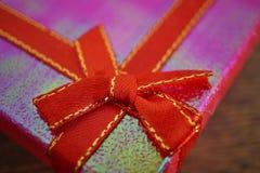 Macrodetail van een rood lint met het gouden stikken die roze aanwezige Kerstmis verpakken Stock Afbeelding