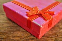 Macrodetail van een rood lint met het gouden stikken die roze aanwezige Kerstmis verpakken Royalty-vrije Stock Foto's