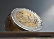 Macrodetail van een zilveren en gouden muntstuk in waarde van twee Euro EUR, Euro op witte en zilveren achtergrond als symbool va Stock Foto's