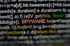 Macrofoto van het computerscherm met programma broncode en benadrukte SPYWARE-inschrijving in het midden Manuscript op Stock Foto
