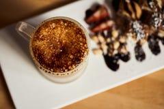 Macrofoto van kop van Hete latte met gebakken karamelkorst en zoet broodje met banaan en aardbei op de houten lijst in coffe- stock afbeelding