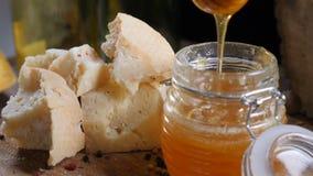 Macrofoto van spaghetti De verschillende soorten kaas en honing in glaskom schikten prachtig op houten achtergrond Honing het gie stock footage