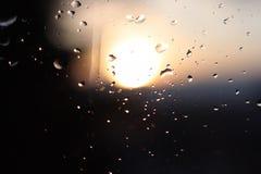 Macrofotografie van regendalingen op het glas op een onscherpe achtergrond van de het plaatsen zon Textuur in donkere en oranje t stock foto