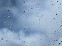 Macrofotografie van regendalingen op het glas op een onscherpe achtergrond van skyy Textuur in donkere en oranje tonen stock foto's