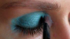Macrolengte - de Vrouw zet heldere blauwe make-up op haar ogen stock video