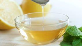 Macrolengte van honing die langzaam van metaallepel druipen in glaskruik op lijst stock footage