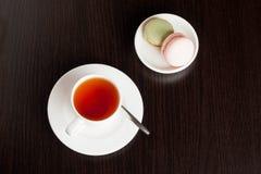 macrons français traditionnels avec le service à thé sur le fond Images stock