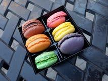 Macroons francese dalla pasticceria locale su una Tabella di patio fotografia stock