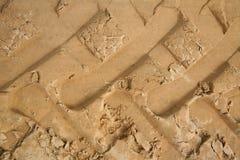 Macrophoto de un fragmento de un camino arenoso-margoso sin pavimentar con los rastros de elementos de la pisada de las ruedas gr Imagen de archivo