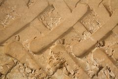 Macrophoto of a fragment of an unpaved sandy-loamy road with traces of elements of the tread of the large wheels of the tractor. Stock Image
