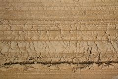 Macrophoto of a fragment of an unpaved sandy-loamy road with traces of the grader. Royalty Free Stock Image