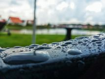 Raindrops on a handle of a chair. Macrophoto of raindrops on a handle of a plastic chair with a backyard, a sky and some buildings in the background Royalty Free Stock Photo