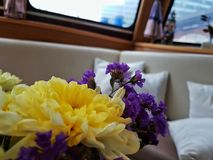 Small bouquet with yellow and violet flowers. Macrophoto of a small bouquet of flowers with some pillows in the background Stock Image