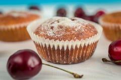 Macroschot van vers gebakken muffin met kersen op wit bureau a Stock Foto's
