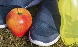 Macroshot od butów, jabłka i butelki z wodą sportów, Obrazy Stock