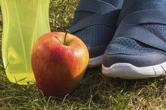 Macroshot od butów, jabłka i butelki z wodą sportów, Zdjęcie Stock