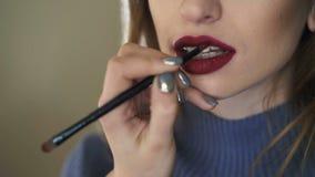 Macrospruit van het toepassen van lippenstift op meisjes` s lippen 4K stock videobeelden