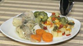 Macrourus fisk med grönsaker på den vita plattan Att tillfoga kärnar ur olja i en mat arkivfilmer