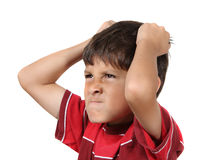 Mad or angry young boy. Mad or frustrated young boy with hands grabbing his hair wearing red shirt on white background Stock Image