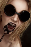 Mad blonde Woman with Black Oil from her Mouth Royalty Free Stock Photos