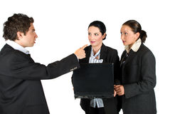 Mad boss with employees. Mad boss screaming at his employees while the two  woman holding and using a laptop and looking very surprised and shocked at him,check Stock Photography