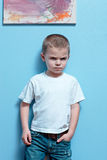 Mad Boy. Little boy mad look on his face standing against a wall royalty free stock photo