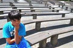 Mad Boy. A little boy is waiting alone and mad in an amphitheater Stock Photos