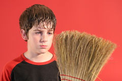Mad boy with broom. Shot of a mad boy with broom royalty free stock photography