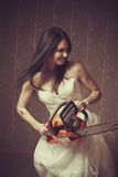 Mad bride. Seductive bride with bloody chainsaw. Indoors shooting royalty free stock photography
