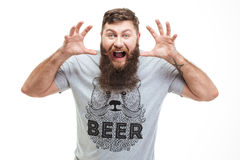 Mad brutal bearded man with raised hands growling and scaring Royalty Free Stock Photography