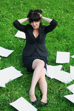 Mad business woman. The business woman has spread out documents on a grass and has clutched at the head Stock Images