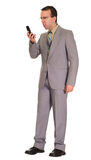 Mad Businessman. Full body view of a businessman getting mad at his cell phone Royalty Free Stock Photography
