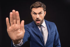 Mad businessman stopping some action. Stop. Angry male boss is stretching arm forward and shouting. Man is standing and looking at camera with irritation Stock Photos