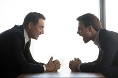 Mad businessmen yell sitting in confrontation at table. Mad businessmen sit at table opposite one another with clenched hands dispute scream at competitor, angry stock images