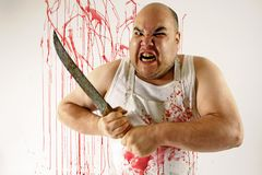 Mad butcher. Crazy insane butcher covered with blood. Harsh lighting for more disturbing feel. Slight motion blur on arms and knife stock photos