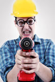 Mad Carpenter with Drill. And yellow helmet on the gray background royalty free stock photo